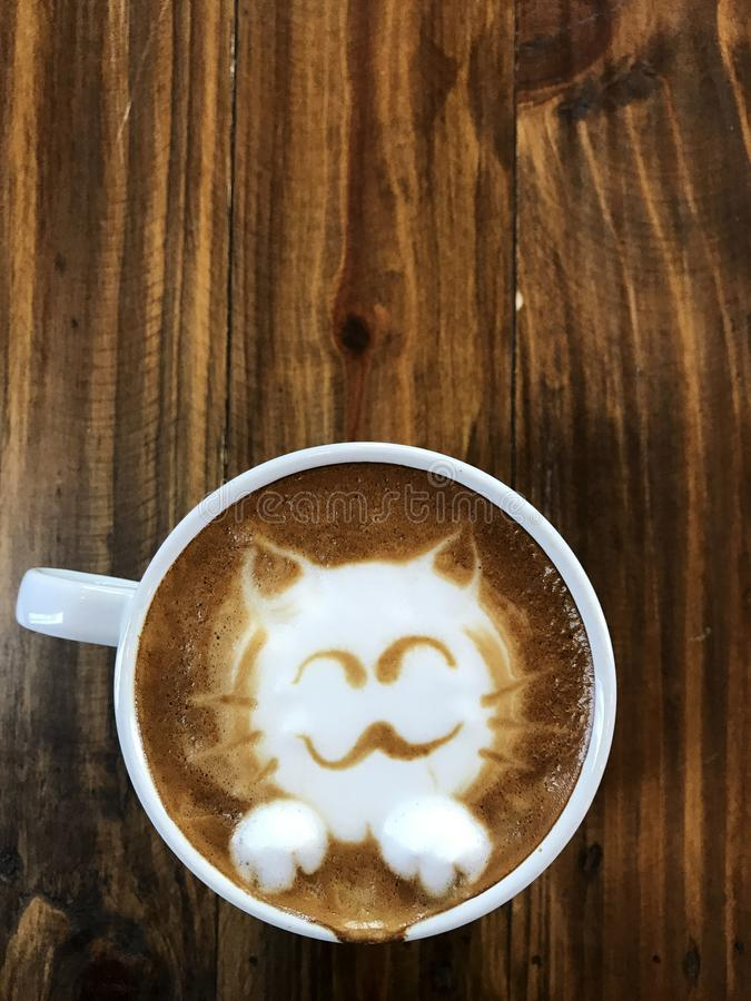 Café lindo del arte del latte de la cara del gato en la taza blanca imagen de archivo