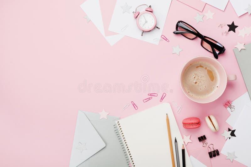 Café, macaron, despertador, material de escritório e caderno na opinião de tampo da mesa pastel cor-de-rosa Configuração lisa Mes fotos de stock royalty free