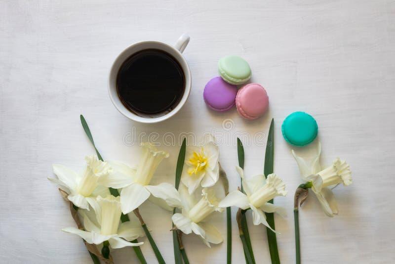 Café, macaron et jonquilles de matin sur un conseil blanc Composition d'un bouquet des jonquilles et des tasses de café image libre de droits