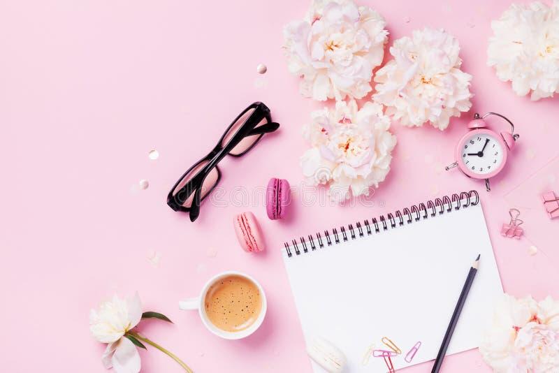 Café, macarrones, despertador, material de oficina, flores de la peonía y cuaderno vacío Escritorio de trabajo de la mujer de la  fotos de archivo