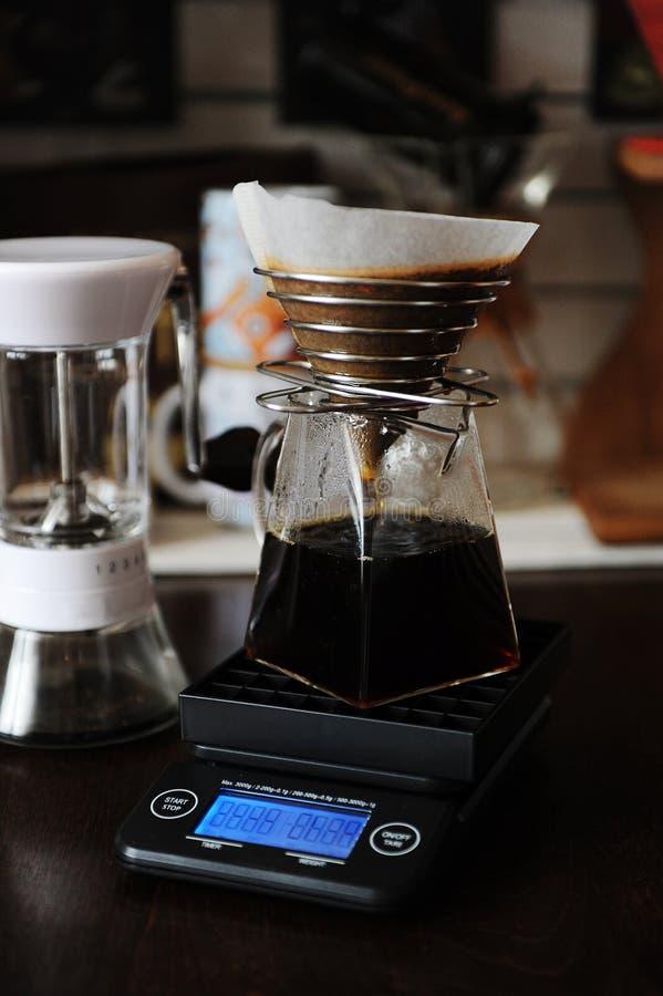 Café manuel alternatif brassant avec le filtre de papier dans le dispositif d'écoulement d'acier inoxydable Sur l'échelle électro photographie stock libre de droits