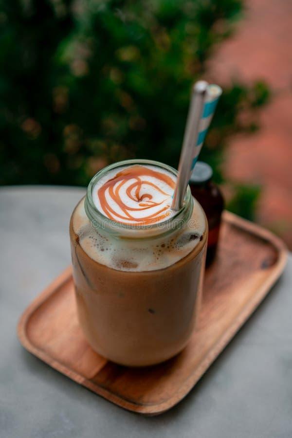 Café mit glas des flach-weißen Kaffees an nahe einigen Blumen stockfotos