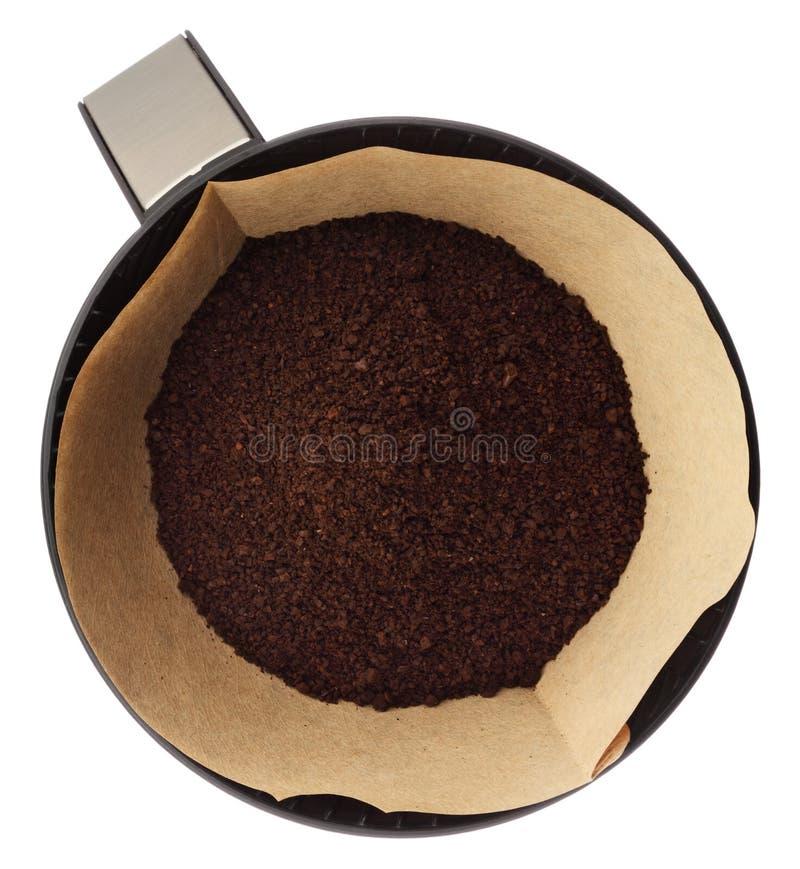 Café molido en el tenedor del filtro aislado en el fondo blanco encima imagen de archivo libre de regalías