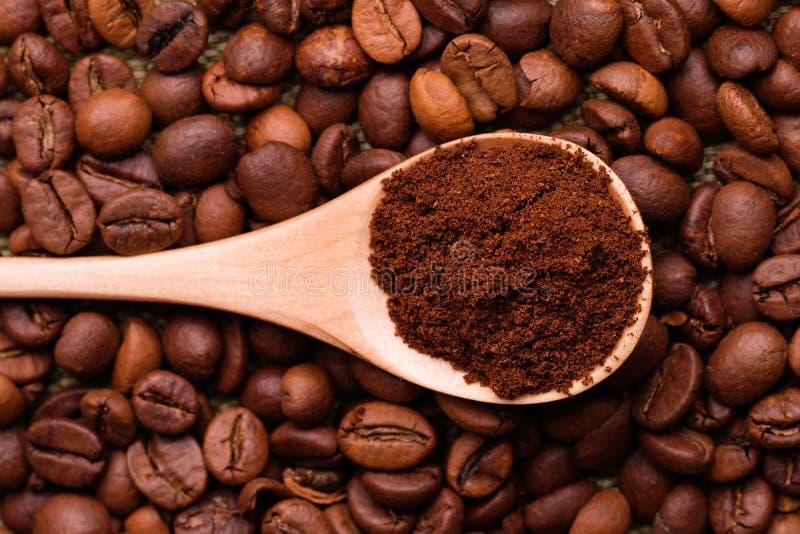 Café molido en una cuchara en el fondo de los granos de café enteros fotos de archivo libres de regalías