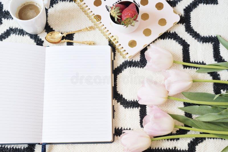 Café, morangos, cadernos no tapete escandinavo Tulipas e colheres cor-de-rosa do ouro Tema preto branco do teste padrão e do ouro fotos de stock royalty free
