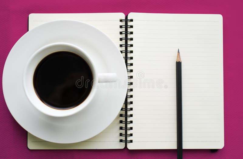 Café no copo branco com livro e lápis do jornal foto de stock royalty free