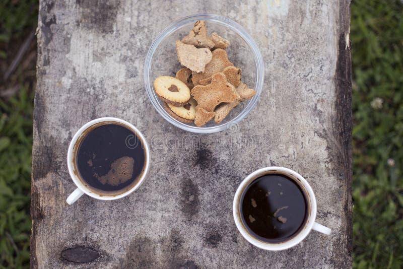 Café no parque com as cookies na tabela de madeira velha imagem de stock royalty free