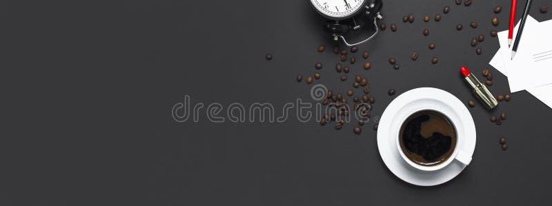 Café noir étendu plat de tasse, grains de café, réveil noir, rouge à lèvres rouge, crayons de couleur, cartes blanches sur l'obsc images stock