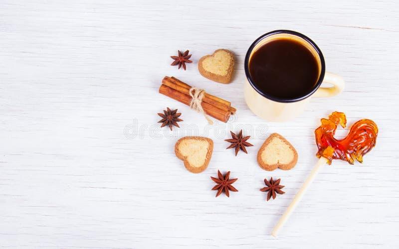 Café noir avec des épices et des bonbons sur un fond en bois blanc image libre de droits