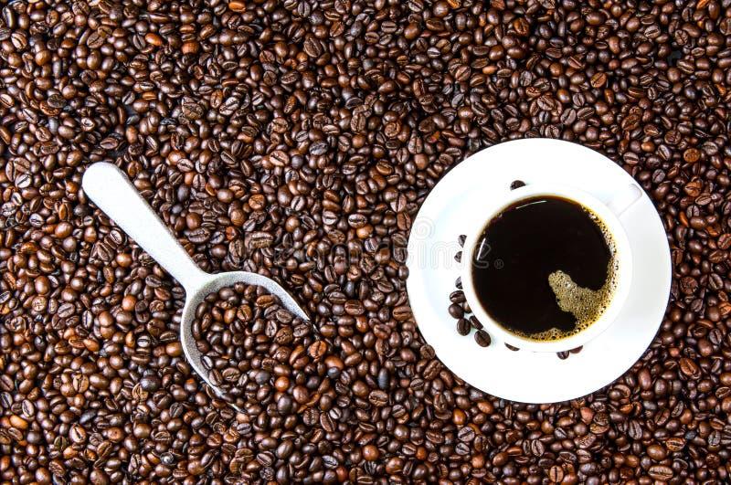 Café noir avec les grains de café rôtis image stock