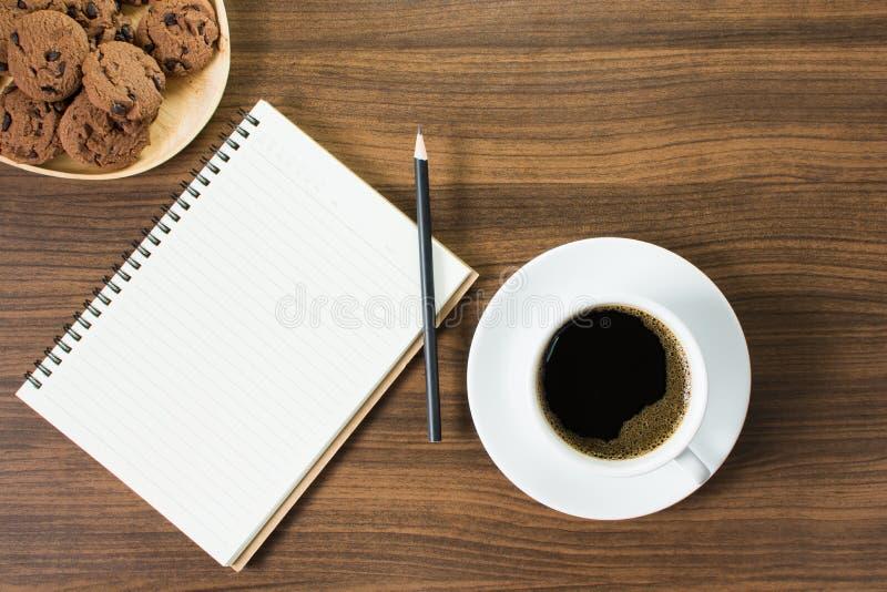 Café noir, biscuits et un carnet avec le travail photographie stock libre de droits