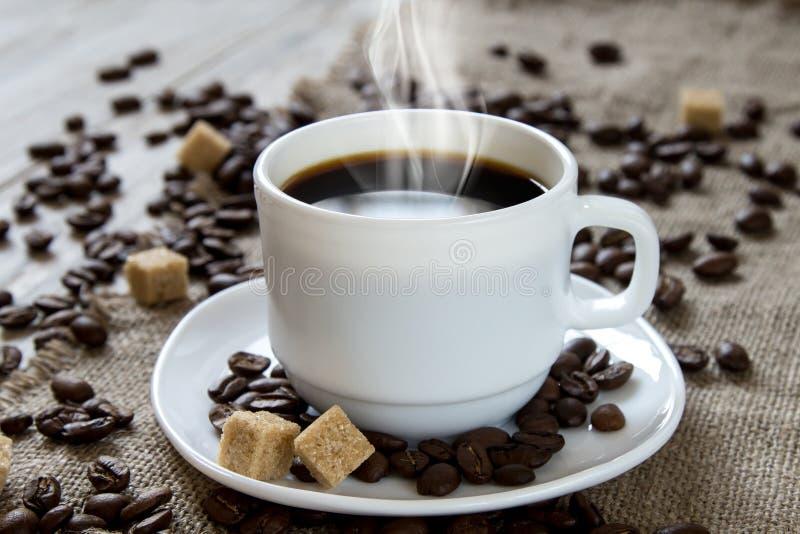 Café noir chaud dans une tasse blanche, un sucre de canne et des haricots rôtis photos stock