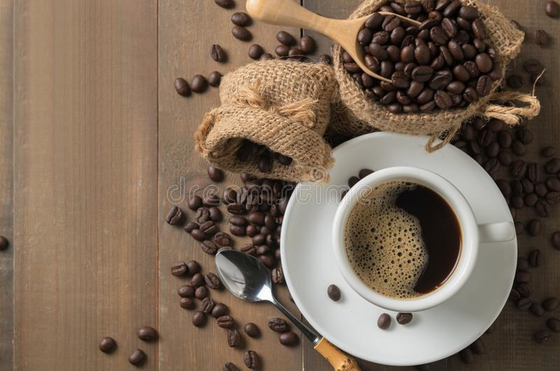 Café noir chaud sur la tasse et les grains de café rôtis dans le scoop en bois o photo libre de droits