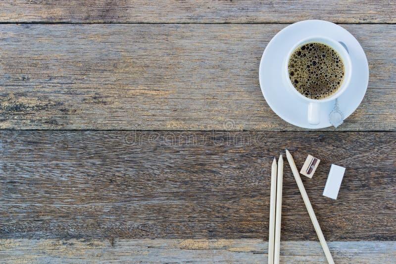 Café noir dans la tasse et des crayons en céramique blancs sur le vieux tabl en bois photographie stock