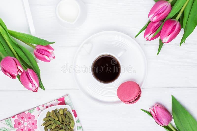 Café noir dans une tasse blanche, un cardamome, des tulipes et un macaron rose ou un macaron de framboise sur un fond en bois Vue photographie stock libre de droits