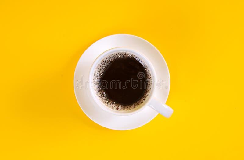 Café noir dans une tasse de café vue sur le dessus sur fond jaune photographie stock libre de droits