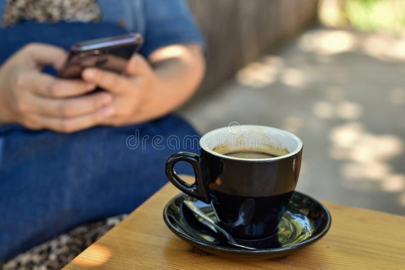 Café noir dans une tasse noire sur la table en bois photo stock