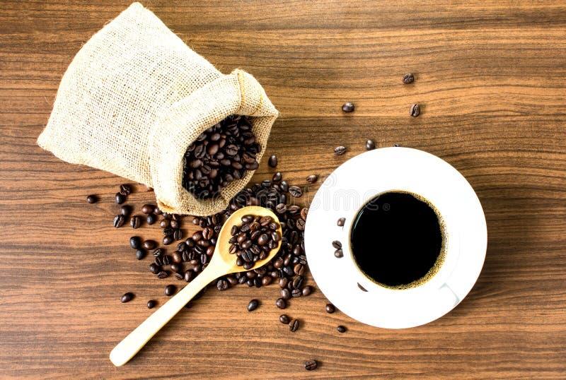 Café noir dedans avec un sac de grains de café rôtis image libre de droits