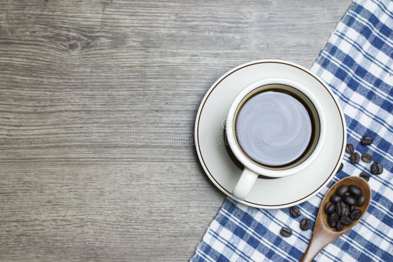 Café noir intense en tasse et grains de café rôtis par scoop en bois de cuillère photos libres de droits