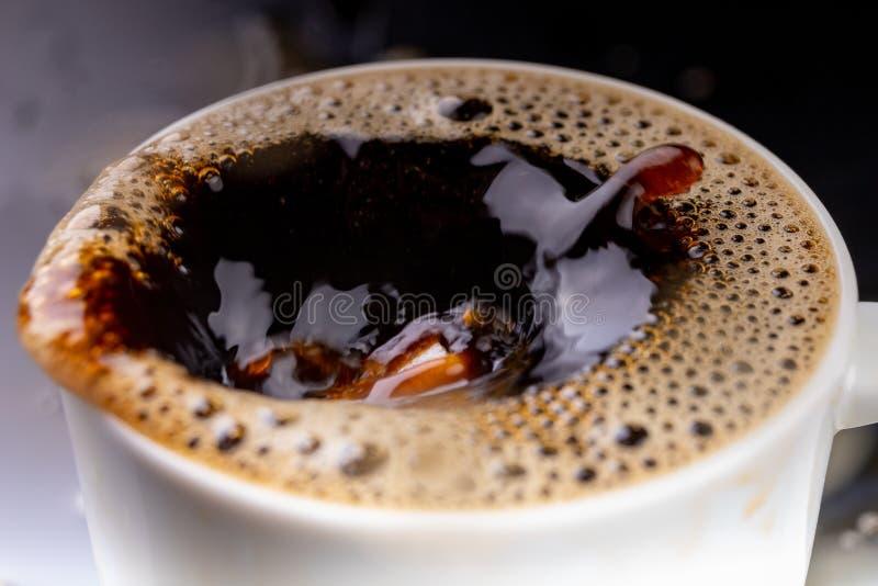 Café noir renversé dans une tasse sur une table noire Mauvaise surface de la boisson dans le conteneur photos stock
