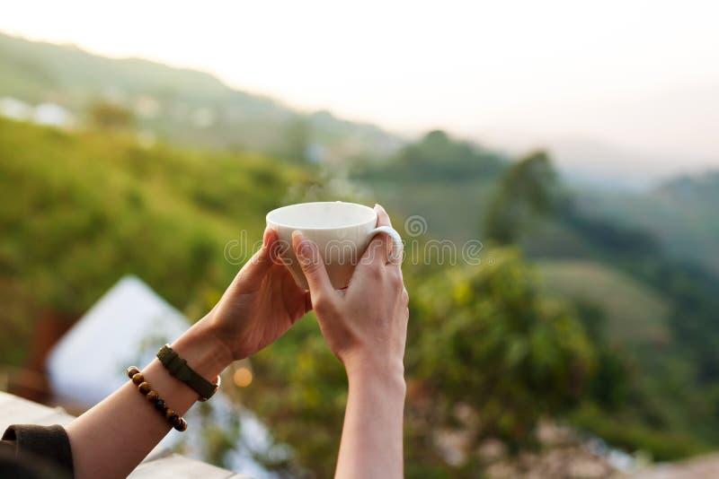 Café o té caliente de la bebida en la mano de la mujer por la mañana en el café al aire libre foto de archivo