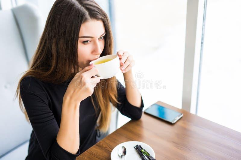 Café o té de consumición de la mujer por la mañana en el restaurante Retrato del primer de la muchacha bonita con la taza de té imagenes de archivo