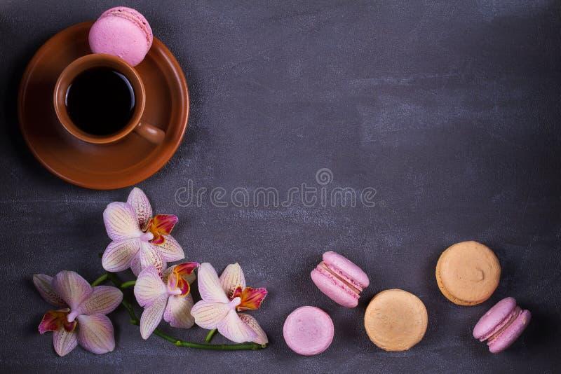 Café, orquídeas y macaron o macarrones de la torta en fondo gris desde arriba foto de archivo libre de regalías