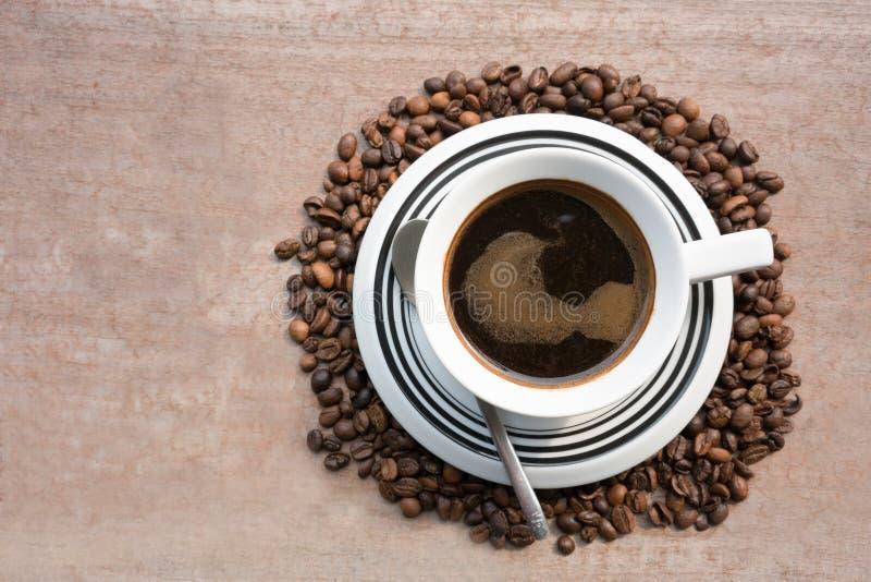 Café oscuro en el medio de los granos de café foto de archivo libre de regalías