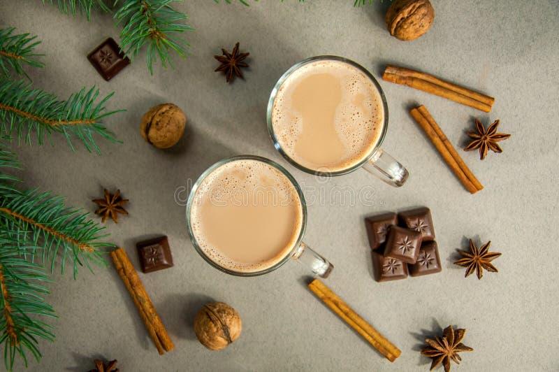 Café ou chocolate quente do cacau da bebida do Natal com leite em um copo pequeno Ramo de árvore do abeto, porcas, anis de estrel fotos de stock royalty free
