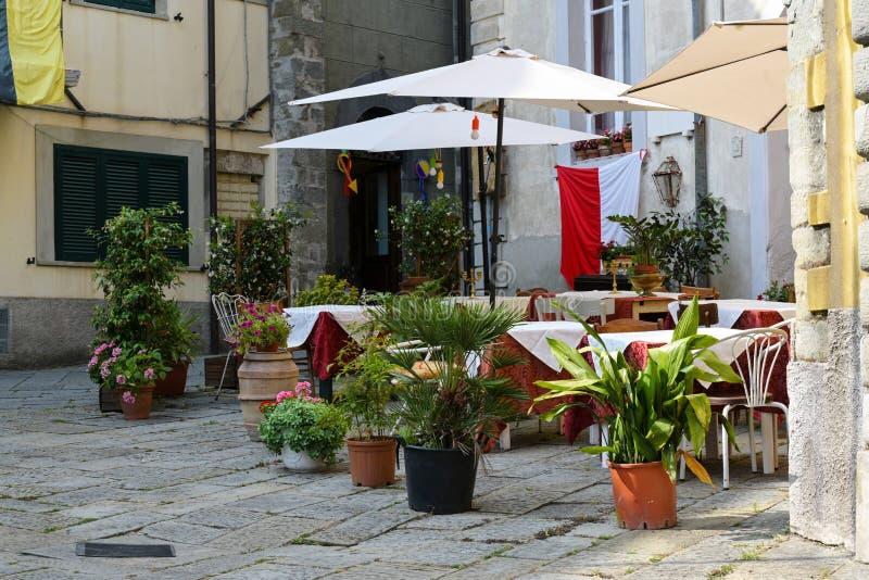 Café ou restaurante da rua com tabelas e os vasos de flores decorados na cidade velha de Fivizzano, uma cidade pequena de Lunigia imagem de stock