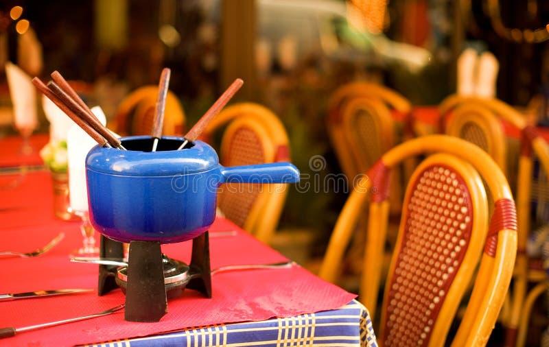 Café parisiense da rua com um potenciômetro do fondue imagem de stock