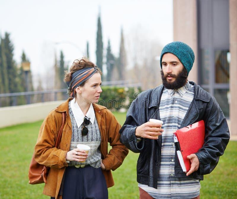 Café parlant et potable de couples de hippie pour aller image stock