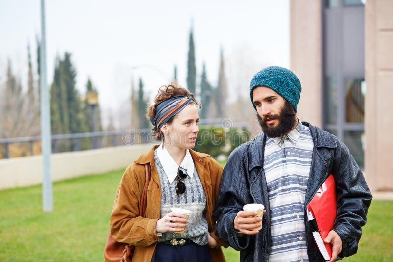Café parlant et potable de couples de hippie pour aller images stock