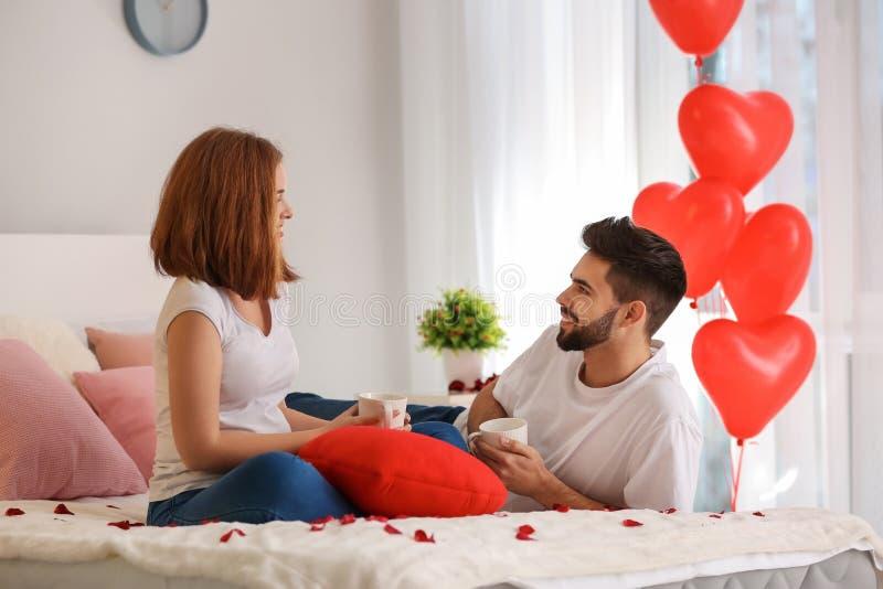 Café potable aimant de jeunes couples sur le lit à la maison Célébration de Saint-Valentin de saint photo stock