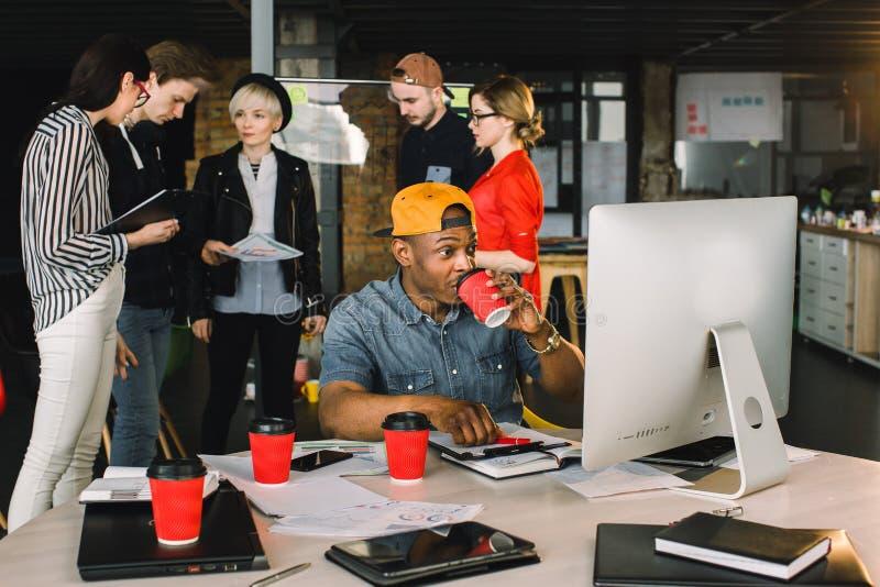 Café potable d'homme africain gai et travail sur l'ordinateur tout en se reposant à la table dans l'endroit moderne de bureau sie image libre de droits