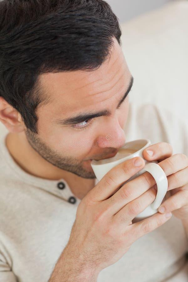 Café potable d'homme bel réfléchi tout en détendant sur le sofa photographie stock