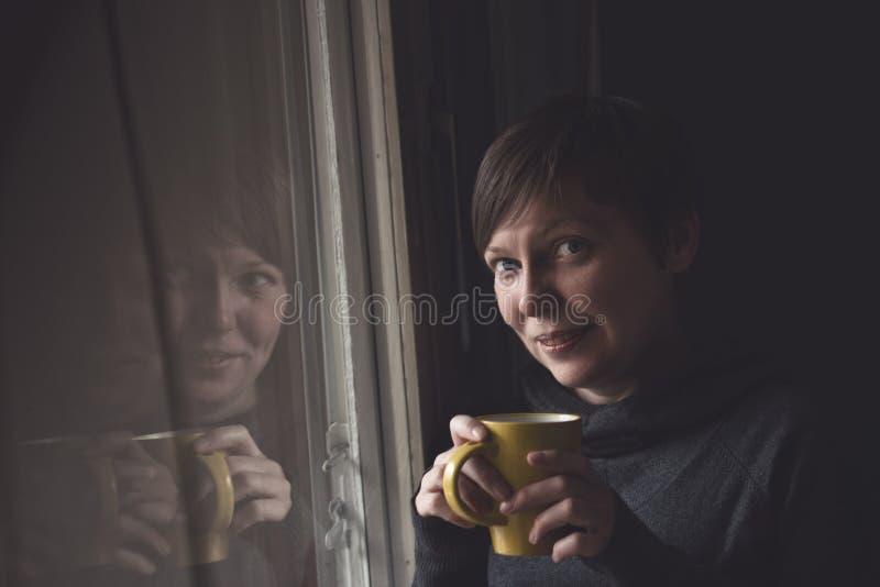 Café potable de belle femme dans la chambre noire photographie stock libre de droits