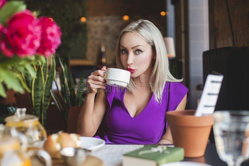 Café potable de belle femme dans le restaurant images stock