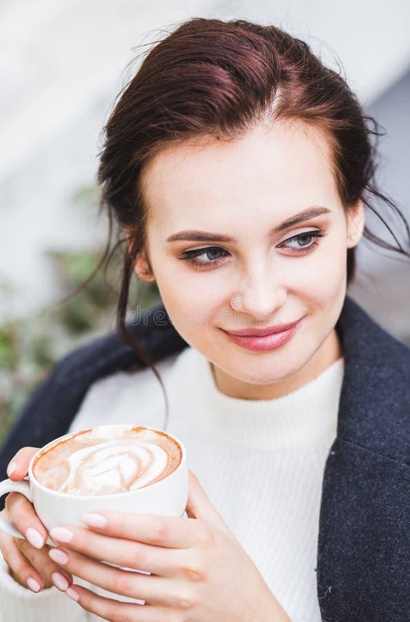 Café potable de cappuccino de belle femme de brune avec la mousse dans le café de rue photo libre de droits