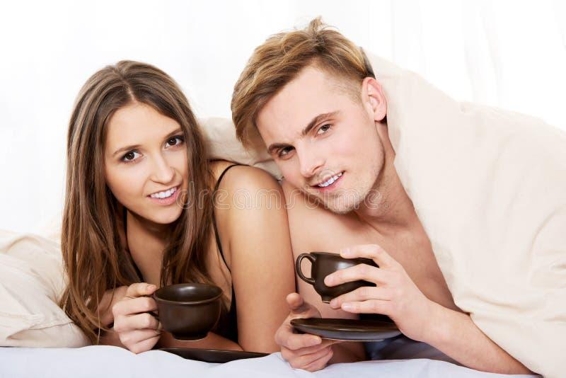 Café potable de couples heureux dans le lit images libres de droits