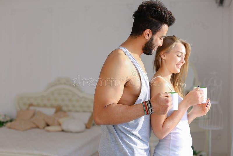 Café potable de femme blonde caucasienne avec l'homme hispanique dans la chambre à coucher photos stock