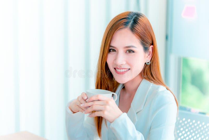 Café potable de femme d'affaires dans des fenêtres de bureau image libre de droits
