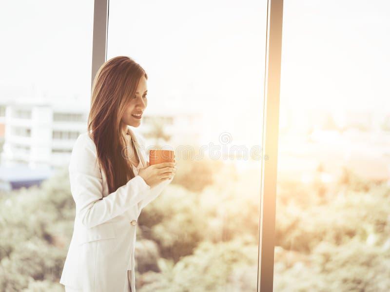 Café potable de femme d'affaires dans des fenêtres de bureau photographie stock
