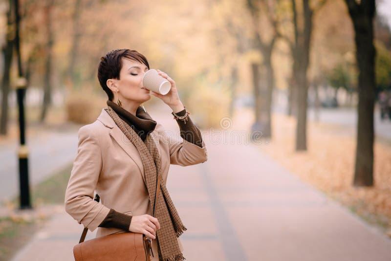 Café potable de femme d'affaires dans la rue d'automne image stock