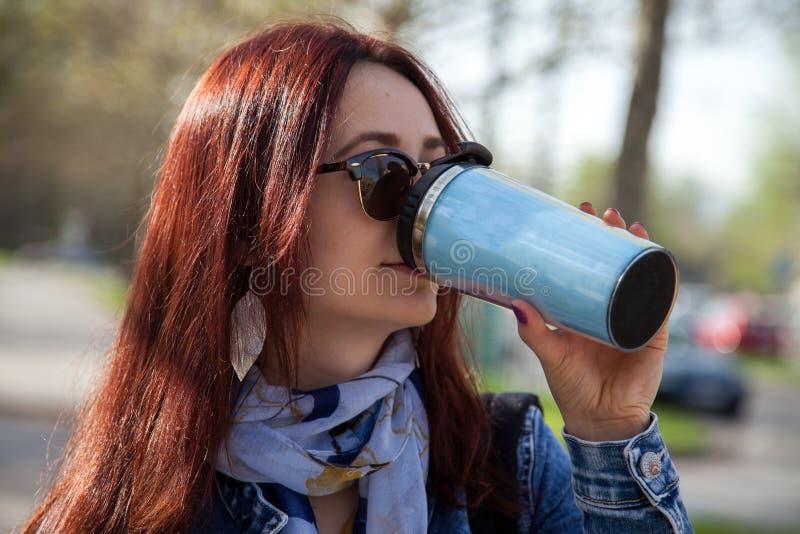 Café potable de femme d'une tasse de voyage photos stock