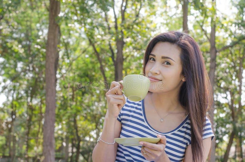 Café potable de femme en parc photos stock