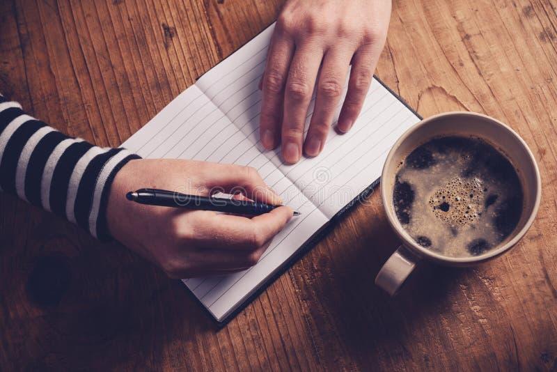 Café potable de femme et inscription d'une note de journal intime photo stock