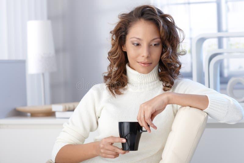 Café potable de femme ethnique à la maison images libres de droits