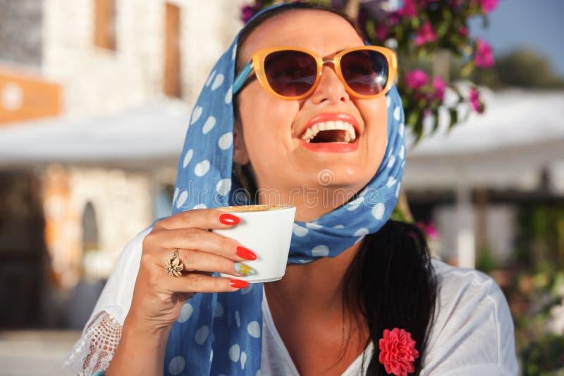 Café potable de femme heureuse dans un café dehors image stock