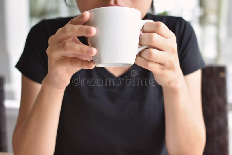 Café potable de femme pendant le matin à la maison photographie stock libre de droits